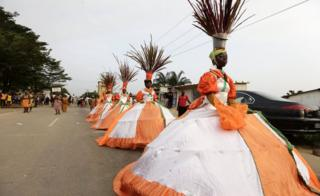 Women parading in wide-skirted costumes and bucket and feather headdresses at a cultural festival in Bingerville, Ivory Coast - Saturday 25 February 2017
