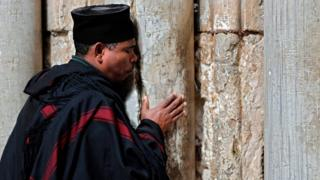 A Christian Ethiopian priest prays next to the closed door of the main entrance of the Church of the Holy Sepulchre in the Old City of Jerusalem on February 26, 2018 after Christian leaders took the rare step of closing the church, seen as the holiest site in Christianity, the previous day at noon