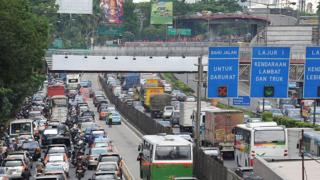 A picture shows an express lane dedicated for special commuter buses running alongside a congested highway in Jakarta