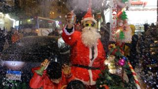 """A man wearing a Santa Claus costume selling Santa Claus dolls as part of New Year""""s Eve celebrations at a market in Cairo, Egypt, 31 December 2017"""
