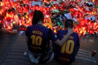 Dos personas sentadas frente a las velas y flores colocadas en Las Ramblas, Barcelona, España, en recuerdo de las víctimas del ataque del 17 de agosto.