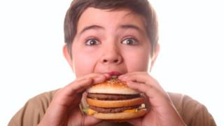 Overweight boy tucking into a burger