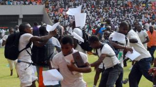 Job-seekers appling for work at the Nigerian immigration department scramble as their exam papers fly in the air, on the pitch of Abuja National Stadium, on March 15, 2014.