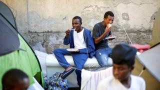 Migrants are fed by an NGO at a makeshift camp in Rome