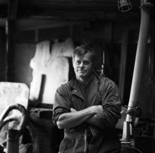 A portrait of a man in overalls