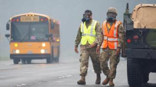 Hawaii National Guard soldiers wear masks to protect themselves from volcanic gases in Pahoa during ongoing eruptions of the Kilauea Volcano in Hawaii, U.S., May 17, 2018