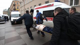 Спасатели несут на носилках пострадавшего от взрыва
