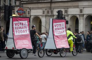 Cyclists with vote remain posters pass Big Ben