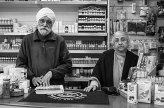 Mr and Mrs Singh Soor stand in their shop