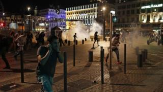 People run after police fired tear gas following clashes after the Euro 2016 soccer championship group B match between England and Russia in Marseille