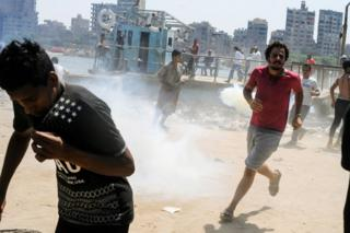 People run for cover from tear gas on the Nile island of al-Warraq, 16 July