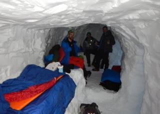 Three men in a snowhole in the Cairngorms