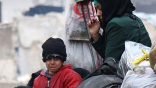 Niño llorando y una mujer esperan ser evacuados de Alepo
