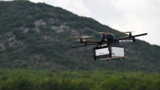 This picture taken on September 28, 2015 shows a Geopost drone flying in Pourrieres, southeastern France, during a presentation of a prototype of a package delivery drone