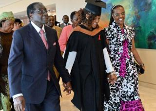 Zimbabwe's President Robert Mugabe (L) and his wife Grace (R) with first-born child and only daughter Bona Mugabe (C) leaving a graduation ceremony at MDIS-University of Wales graduation ceremony in Singapore - 16 November 2013
