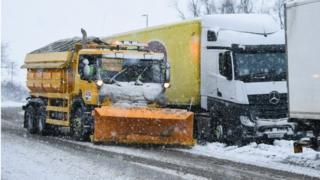A snow plough clears snow on a slip road next to the M74