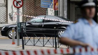 Un policía vigila la calle donde se encuentra el auto en el estaba Papademos cuando se produjo la explosión.