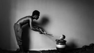 Picha hii kwa jina Asylum yake Eric Gyamfi kutoka Ghana inamuonyesha mwanmme akiwa na makasi huku akimsongelea mvulana aliyeko ndani ya nyungu