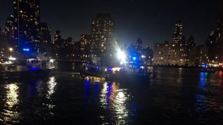 A dark and blurry photo of a small ship on the New York East River