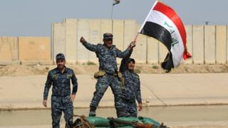 Iraqi forces pose with a national flag as they stand on a river bank across from Kurdish Peshmerga positions on October 14, 2017, on the southern outskirts of Kirkuk.
