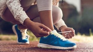 Женщина завязывает шнурки