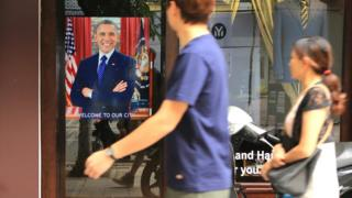 """A Vietnamese couple pass a poster of U.S President Barack Obama with footnote read """"Welcome to our city"""""""