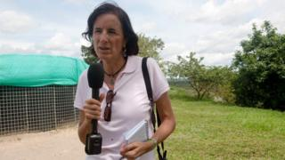 file picture of Salud Hernandez Mora outdoors, holding a microphone and a pen, and with a camera hanging from her wrist