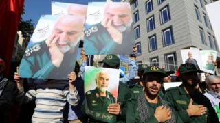 Iranian men, including members of the Revolutionary Guards, hold portraits during the funeral of Brigadier General Hossein Hamedani in Tehran on 11 October 2015