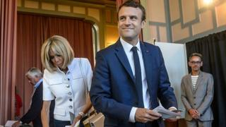 French President Emmanuel Macron (R) votes with his wife Brigitte Trogneux in Le Touquet, northern France, 11 June 2017