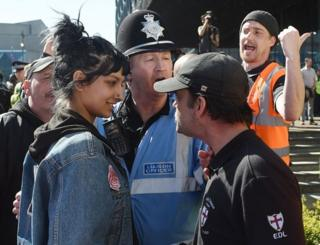 """A viral photo of a woman smiling at an English Defence League (EDL) protester in Birmingham was snapped after she stepped in to defend a """"fellow Brummie"""", she has told the BBC."""