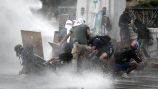 Protesters react as they get hit by water jets during a protest in Caracas, Venezuela, 07 June 2017.