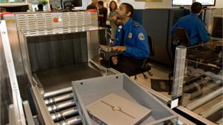 A Transportation Security Administration (TSA) officer reads the X-ray of a laptop computer at Baltimore-Washington International Airport.