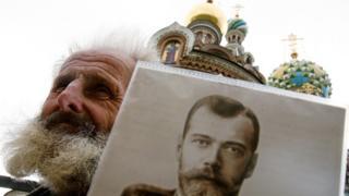 Un hombre con un retrato de Nicolás II