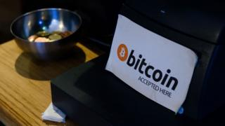 A coffee shop sign advertises that the digital currency 'Bitcoin' is accepted in central Dublin
