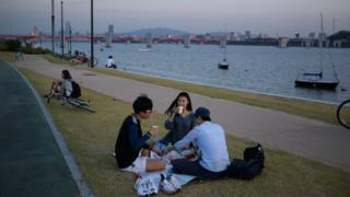 People sit on the grass alongside the Han river