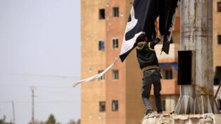 A member of the US-backed Syrian Democratic Forces (SDF) removes an Islamic State group flag in the town of Tabqa on April 30, 2017,