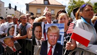 People holding portraits of US President Donald Trump and Polish President Andrzej Duda wait at Krasinski Square in Warsaw, 6 July