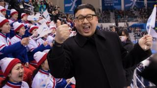 A Kim Jong-un impersonator gives a thumbs-up to the camera as Korea fans look on angrily