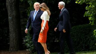 US President Donald Trump looks back toward his wife Melania and Vice-President Mike Pence as he departs the White House