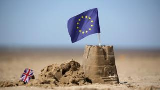 флаги ЕС и Британии на замке из песка