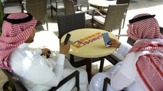 Saudi men explore social media on their mobile phones in a cafe in Riyadh