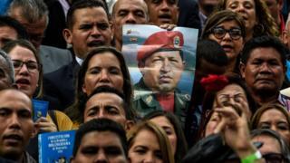 Los nuevos legisladores sostienen un cartel con el retrato de Chávez.