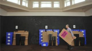 A man walking past ballot boxes to be used for the EU referendum