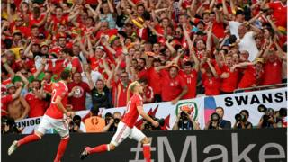 Fans go wild after Aaron Ramsey (r) scores an early goal to put Wales ahead