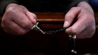 католический крест в руках священника