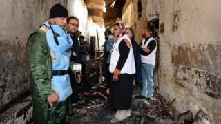 Workers stand in a charred corridor in the damaged hospital