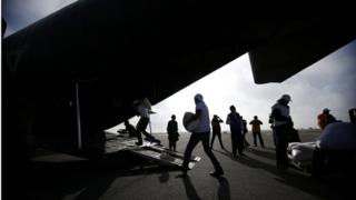 Workers unload sacks filled with grain from a C-130 Hercules aircraft to be distributed in impoverished communities of Oaxaca state on 1 July 2016.