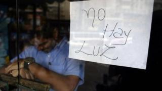 """An employee of a business closed during a blackout stands behind the door with a notice reading """"There's no electricity"""" in Caracas on 3 September, 2013"""
