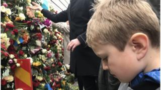 Garoto em frente a memorial a vítimas de ataque em Estocolmo