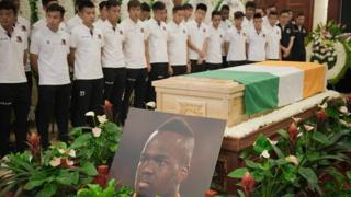 """Beijing Enterprises club football players look at the coffin of Cheick Tiote during a memorial service in Beijing on June 13, 2017. Tiote, who was a member of the Ivory Coast squad that ended a 23-year drought to win the 2015 Africa Cup of Nations, died on June 5, 2017 after """"suddenly fainting"""" during a training session with his second tier Chinese club Beijing Enterprises."""